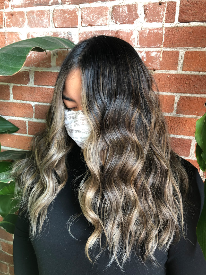 Long dark hair with blonde balayage on masked model on a brick background